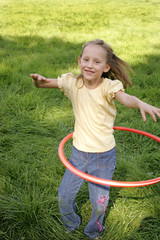 A young girl hula hooping.