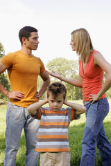 A young boy closes his ears as his parents argue.