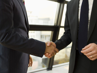 Two businessmen shake hands.