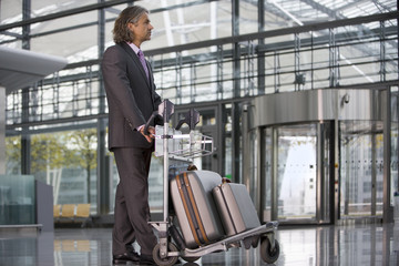 A businessman standing at the airport with his luggage.