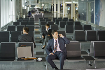 Three businesspeople sitting in the airport.