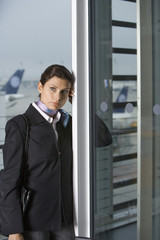A businesswoman leaning on a door at the airport.
