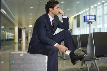 A businessman waiting in the departure lounge.