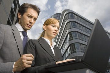 A businessman and woman using a laptop.