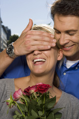 A man covering a woman's eyes and giving her roses.