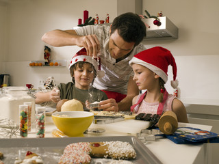 Father baking cookies with his children.