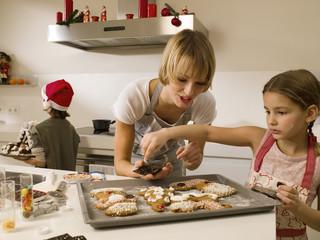 Mother baking cookies with her children.