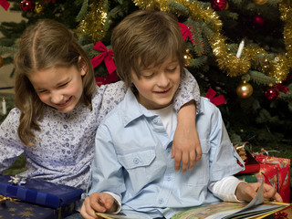 Siblings sitting in front of a Christmas tree.