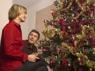 A couple decorating a Christmas tree.