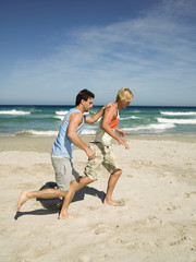 Two men jogging on the beach.