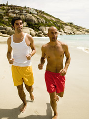 Men jogging on the beach.