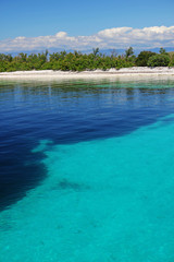 Coast in smooth water. Azure clean water