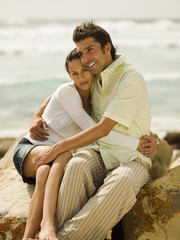 Couple sitting on the rocks at a beach.