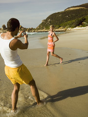 Man taking pictures of his girlfriend on the beach.