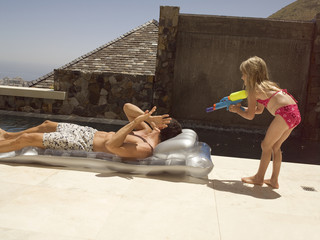 A girl squirting water on her father.