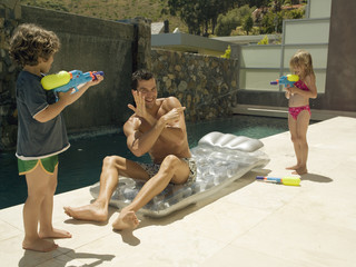 Children squirting water on their father.