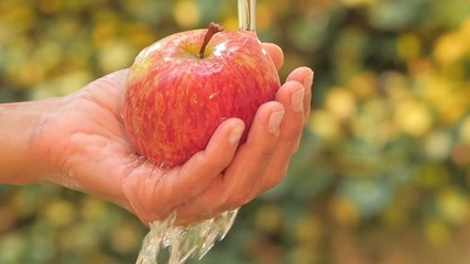 red apple in hand under flowing water slow motion