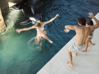 Man pushing woman into the pool.