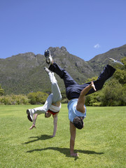 Two men doing hand stands