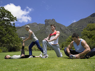 Two young couples exercising on a lawn