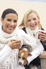 Portrait of two young women holding tea cups with a dog and smiling