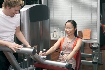 Trainer helping a woman in the gym.