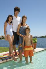 Siblings standing by the pool.