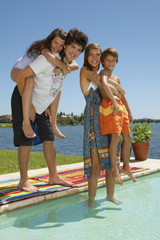 Siblings standing by the pool.