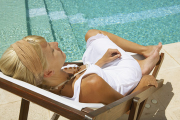 A woman sitting by the pool.