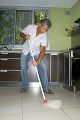 Man mopping the kitchen floor.