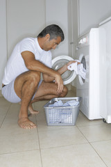 Man putting clothes in the washing machine.