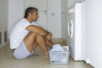 Man sitting in front of a washing machine.