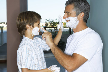 Father and son applying shaving foam.