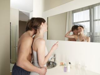 Man hugging girlfriend applying make up.