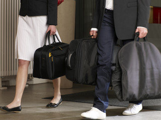 Couple carrying their luggage in a hotel.