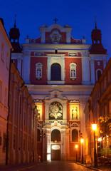 Baroque facade of the parish church in Poznan by night .