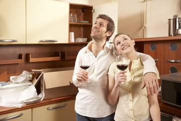 Young couple holding glasses of red wine in the kitchen