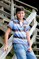 Nice preteen boy smiling in wooden stairs