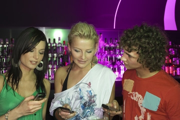 Close-up of three people holding their mobile phones at a bar counter