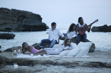 Two young men and three young women on the beach