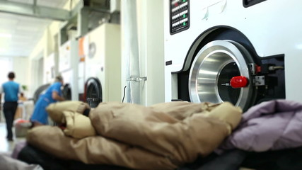 Worker loads dirty clothes in washing machine