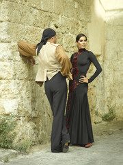 Two female dancers standing near a stone wall