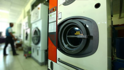 Worker checks washing machines in laundry room