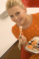 Portrait of a young woman eating food with a pair of chopsticks