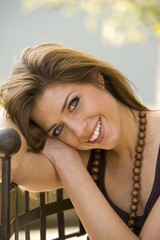 Portrait of a young woman leaning on a grille and smiling