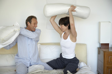Mature couple having a pillow fight on the bed