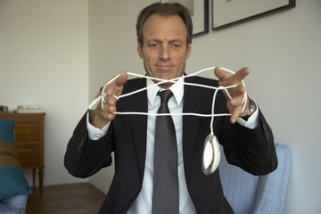 Mature man tangled in a computer mouse wire