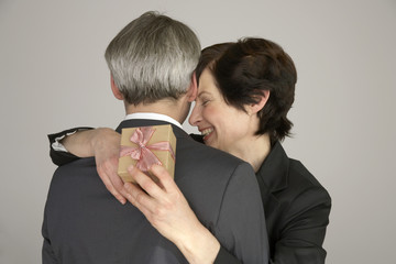 Woman embracing a man with a gift in her hand