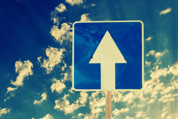 Toned image of directional road sign outdoors against sky