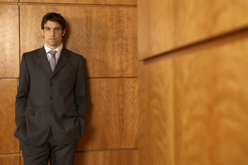 Portrait of a businessman standing and leaning against a wall